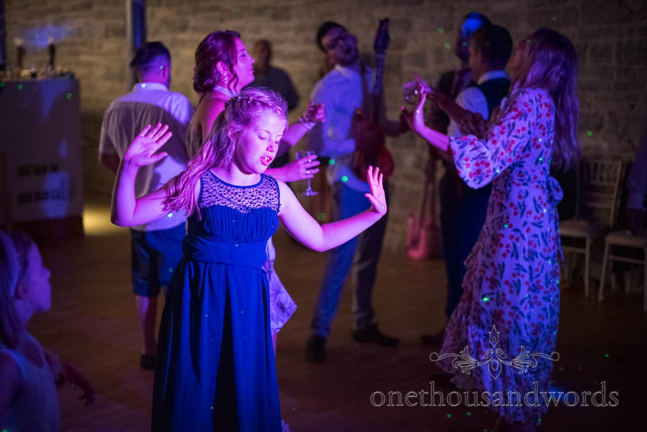 Bridesmaid and wedding guests dance and sing with their arms in the air on dance floor lit with blue disco lights