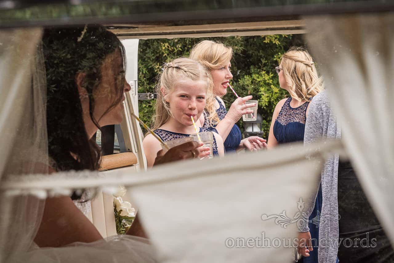 Bridesmaid drinking with straw is photographed through wedding camper van window by one thousand words wedding photography