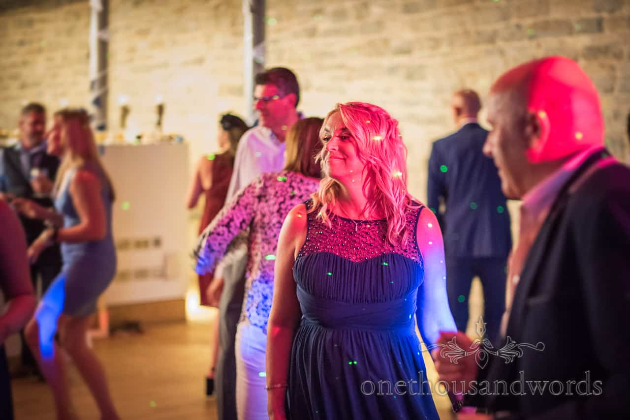 Bridesmaid in navy blue dress and wedding guests dance lit red on wedding dance floor with green lazer dots