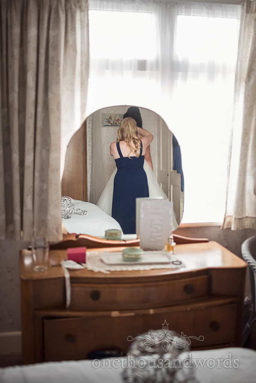 Reflection of bridesmaid in blue dress helping bride into her wedding dress in shaped mirror in bright window photograph