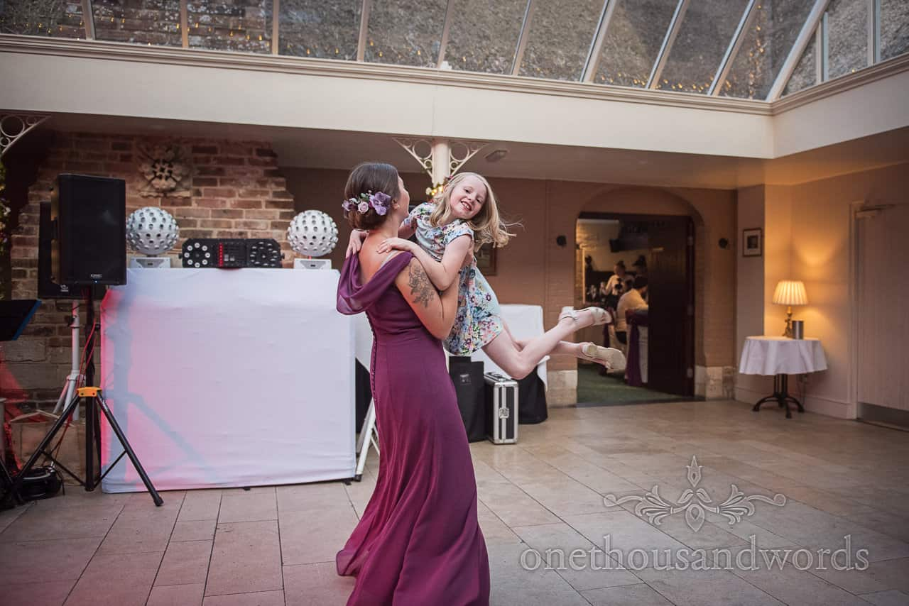 Bridesmaid in purple dress lifts child high into the air on the dance floor whilst dancing in Dorset wedding venue