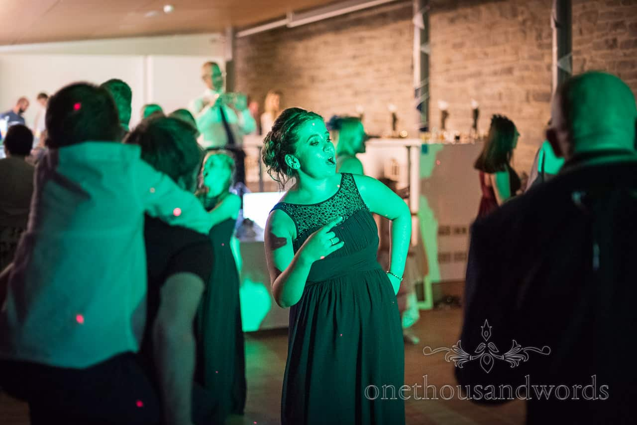 Bridesmaid sings to wedding music and pulls dancing shapes whilst lit with green lights on wedding dance floor