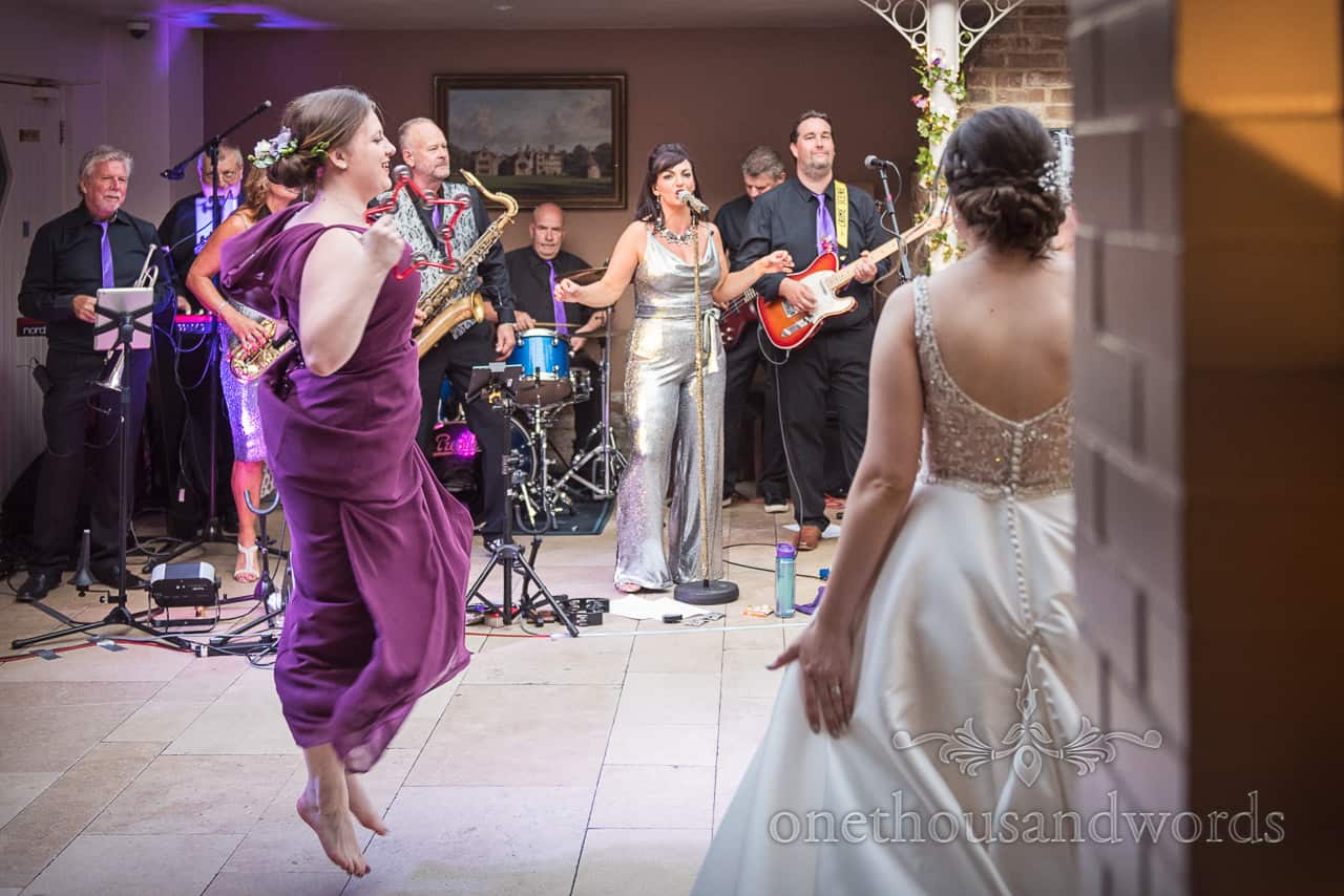 Bridesmaid in purple dress next to bride in white wedding dress jumps into the air whilst dancing to the wedding band