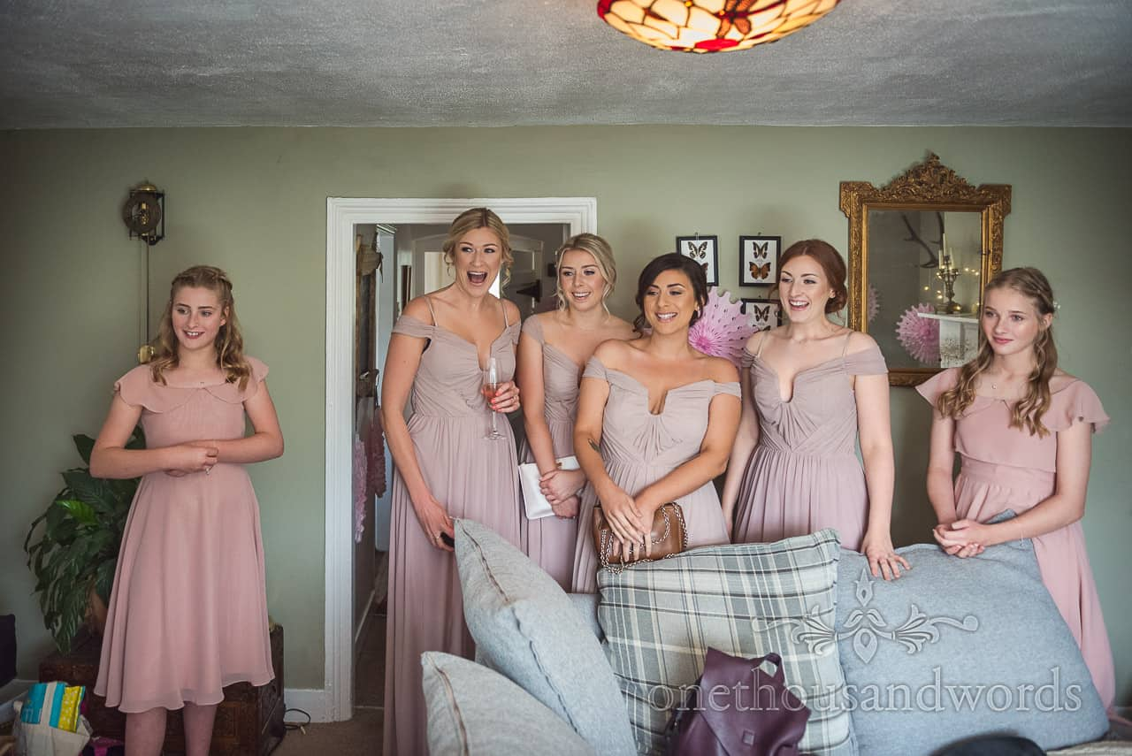 Bridesmaids excited reaction to seeing bride in wedding dress for the first time photograph by one thousand words photography