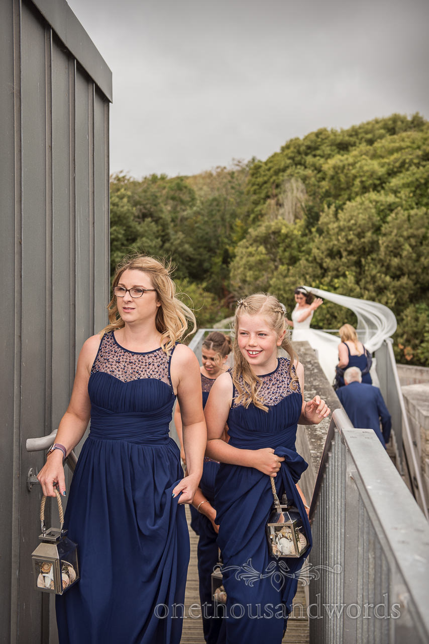 Bridesmaids in navy blue dresses climb wedding venue stairs whilst the bride's white veil blows in the wind in the background