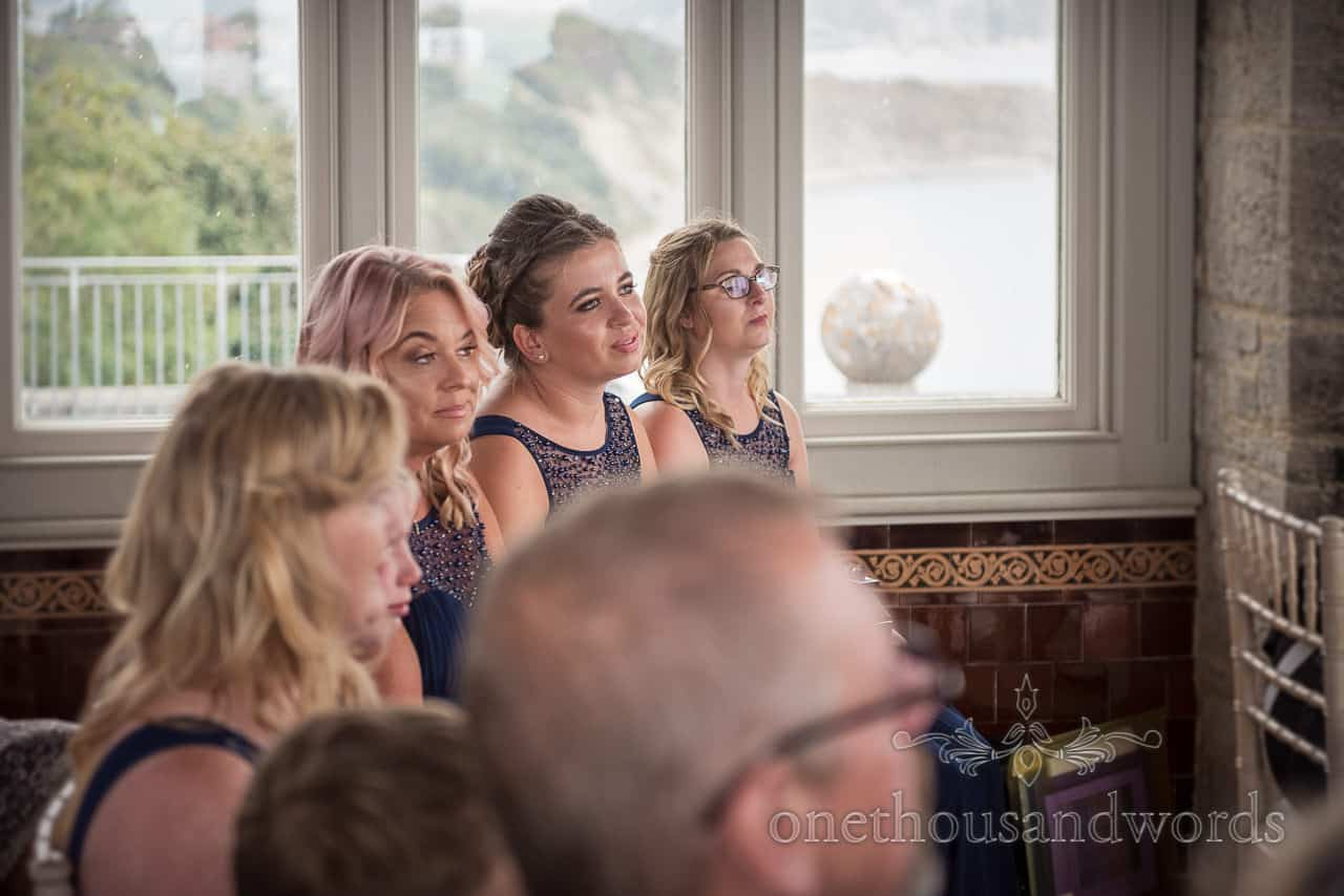 Bridesmaids in navy blue matching dresses watch civil wedding ceremony photograph by one thousand words wedding photography