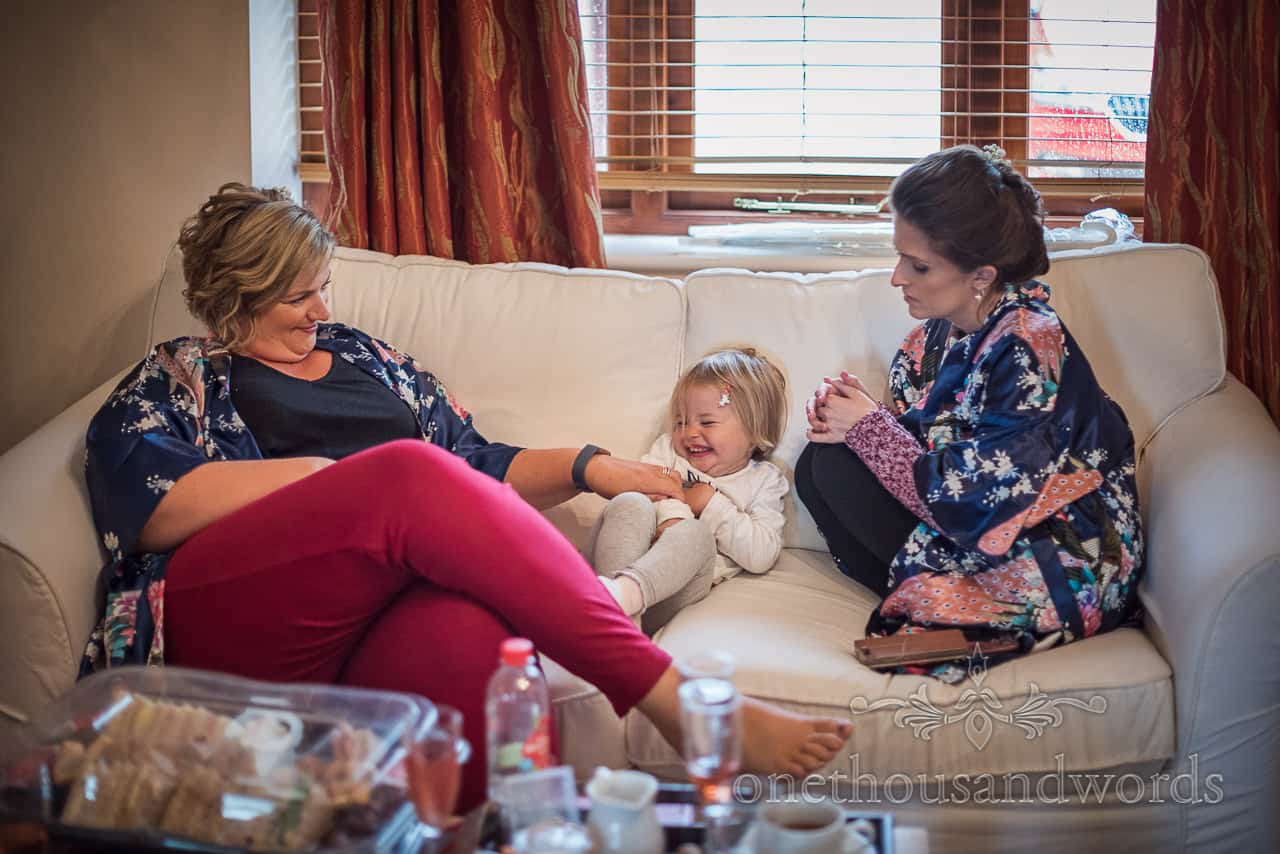 Bridesmaids tickle flower girl on sofa during wedding morning preparation photographs at Kingston Country Courtyard bridal suite
