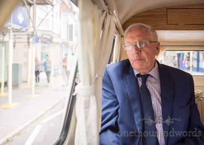 Calm father of the bride looks out of VW camper van wedding transport window on route to wedding venue photo by one thousand words
