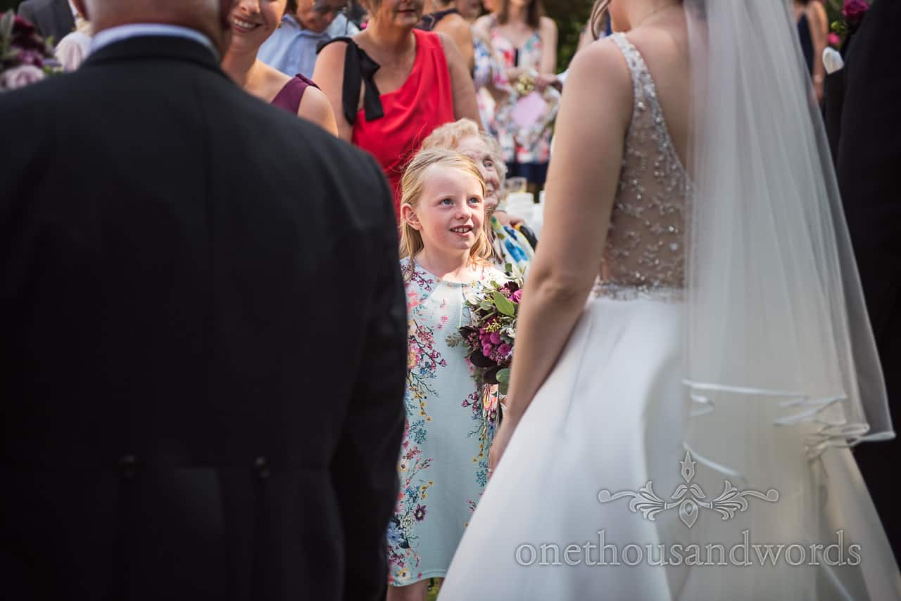 Child wedding guest in light blue dress with floral pattern greets bride during traditional wedding receiving line