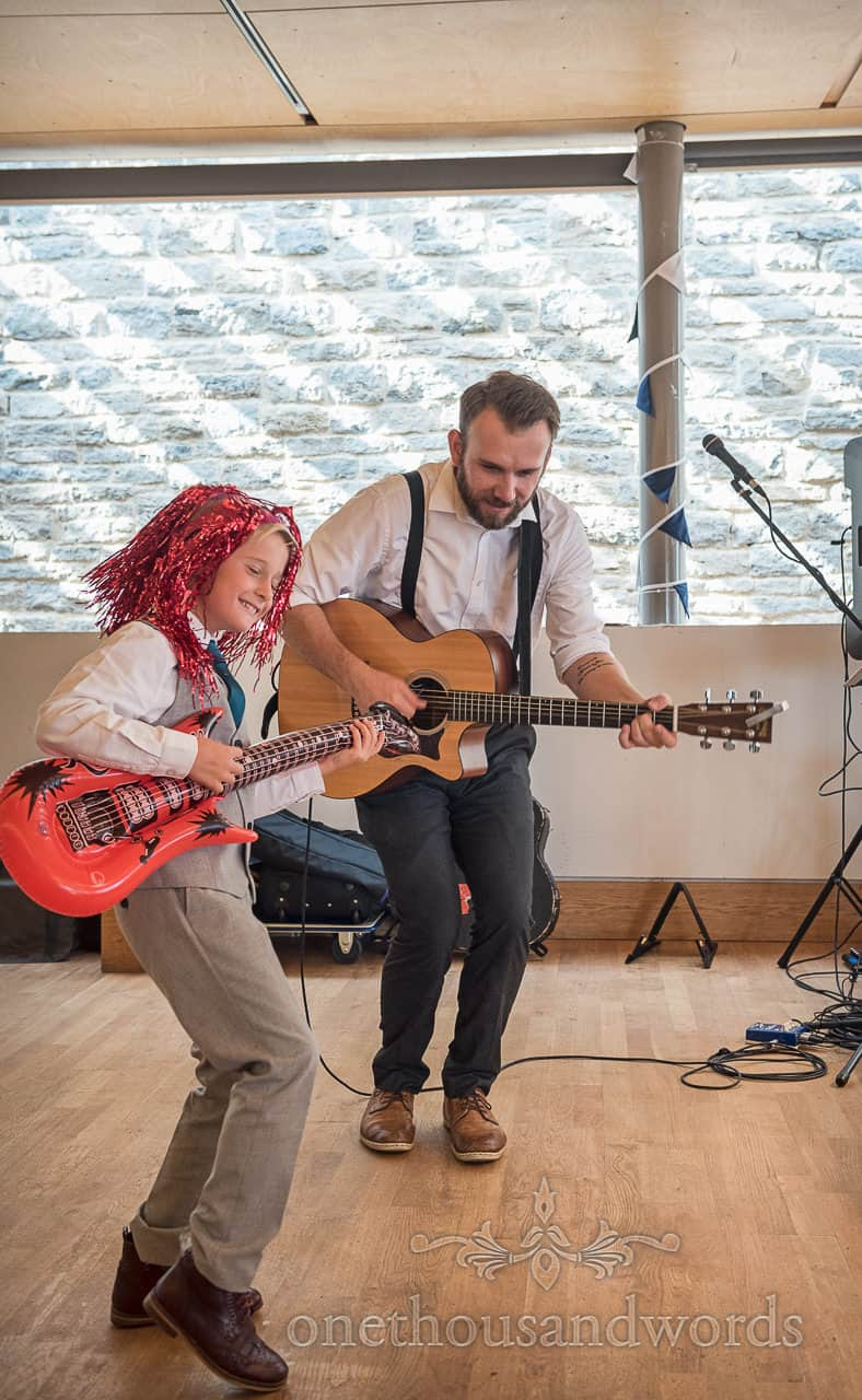 Child wedding guest plays inflatable guitar wearing shiny wig with wedding musician on acoustic guitar during drinks reception