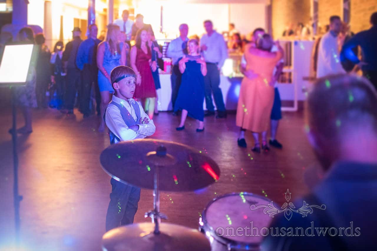 Child wedding guest with tie on head stands on dance floor watching the wedding band under multi colour disco lighting