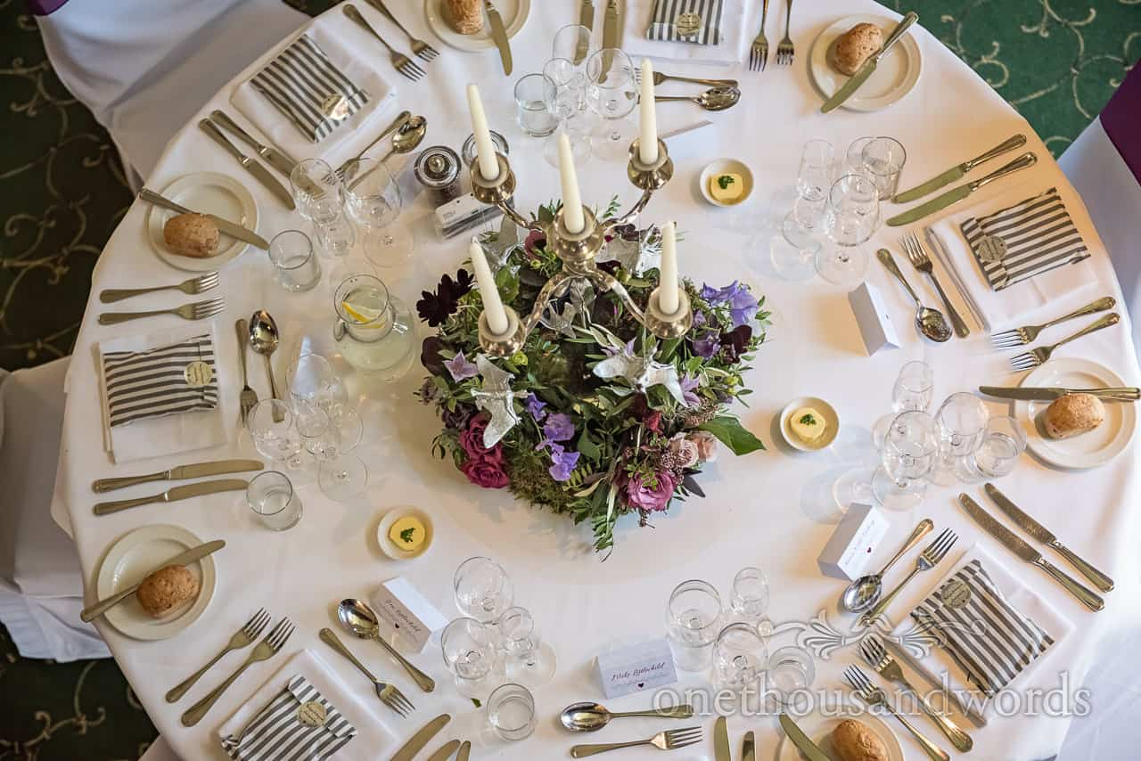 Circular wedding breakfast table laid out with silver Pterosaurs in purple floral center piece with candles by one thousand words