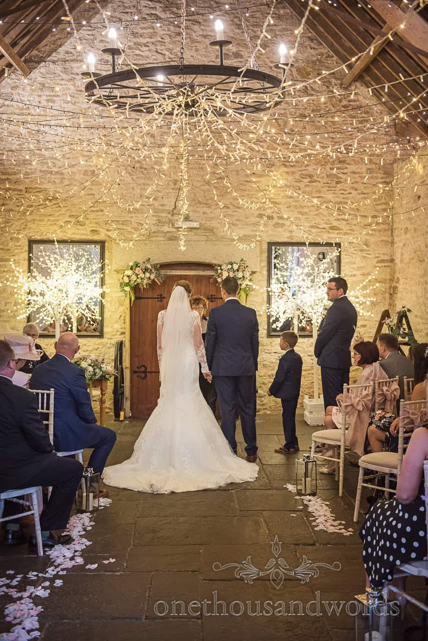 Bride and groom hold hands under fairy lights with fairy light trees at Kingston barn civil wedding ceremony in Dorset