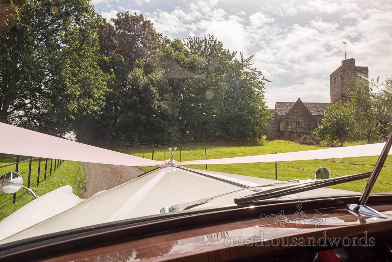 Wedding photograph taken from vintage wedding car as it approaches a Dorset hamlet church wedding venue
