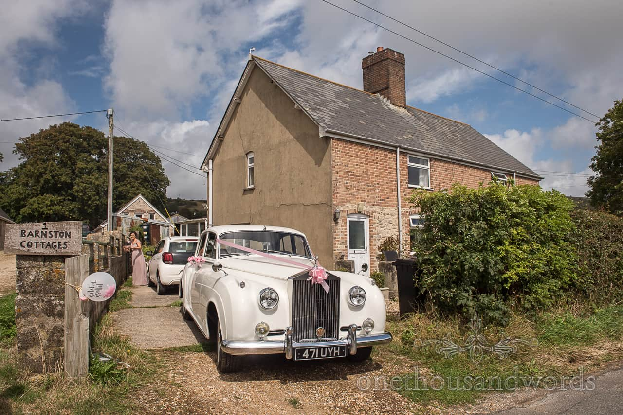 Vintage white Rolls Royce wedding car with pink ribbons out side bridal morning preparation Venue in Dorset countryside