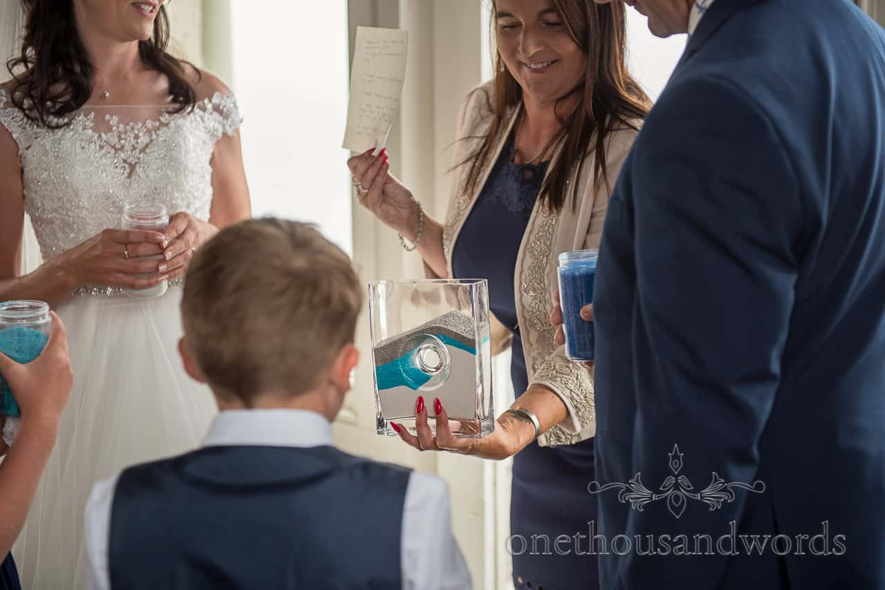 Registrar holds glass vase for multicoloured family sand ceremony at wedding photograph by one thousand words wedding photography