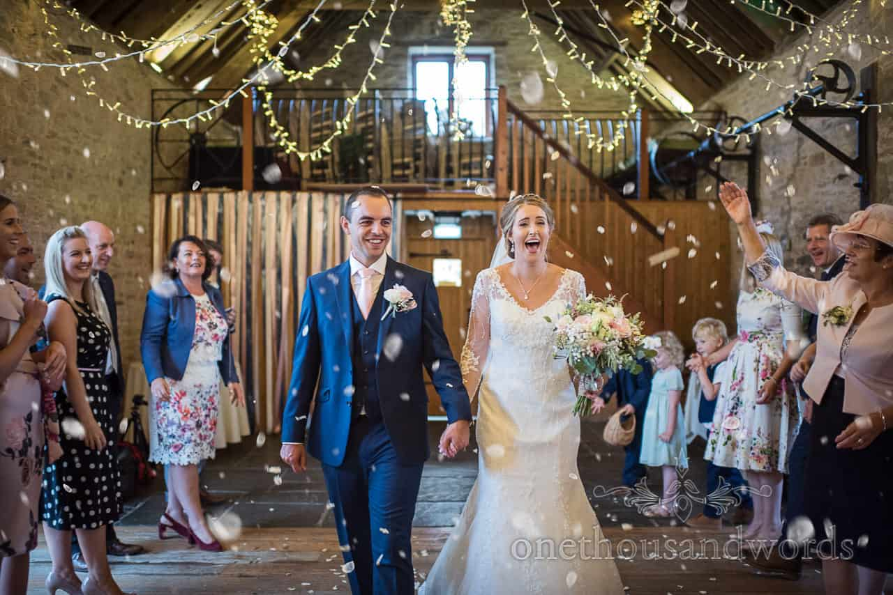 Bride and groom walk under a confetti petal shower from Kingston barn wedding photographs by one thousand words photographers