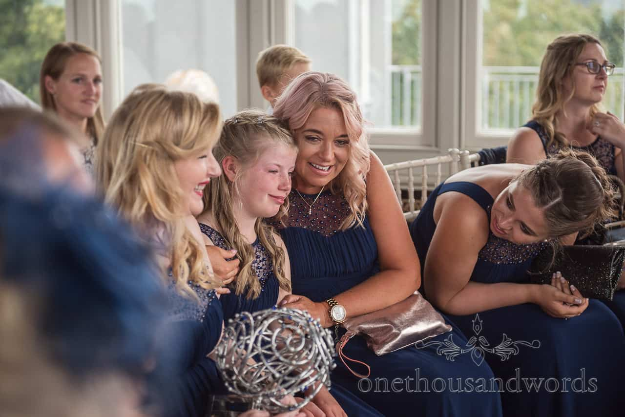 Crying daughter bridesmaid is comforted by other bridesmaids in blue dresses during Purbeck castle wedding ceremony
