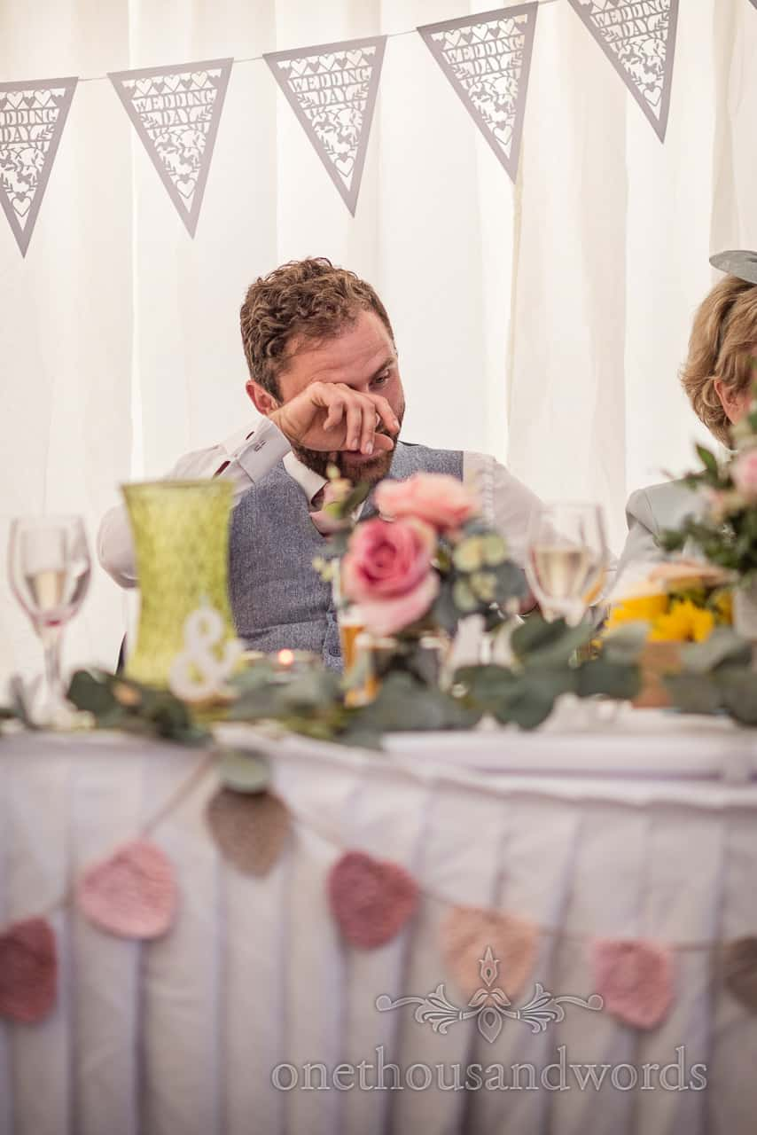 Groom crying and rubbing tears away during best man's wedding speech in marquee photograph by one thousand words