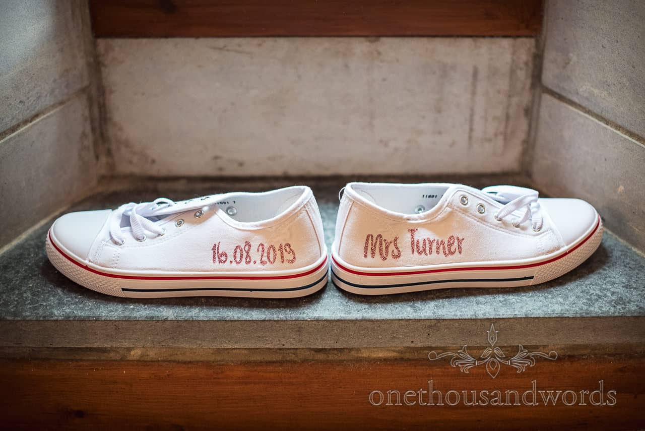 Wedding detail photograph of custom white bridal wedding trainers with glitter script of name and wedding date