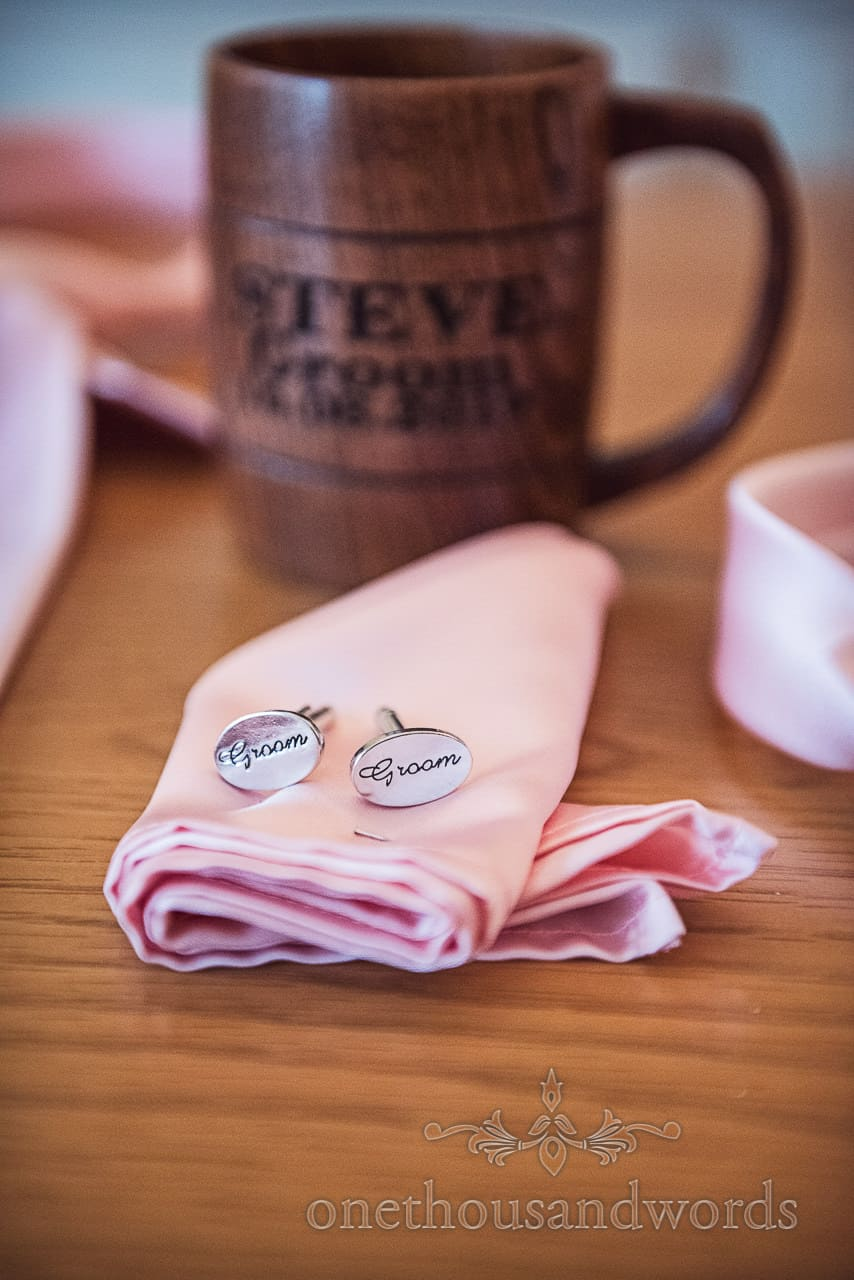 Wedding detail photograph of custom silver groom script cufflinks with wooden beer tankard as wedding morning gifts