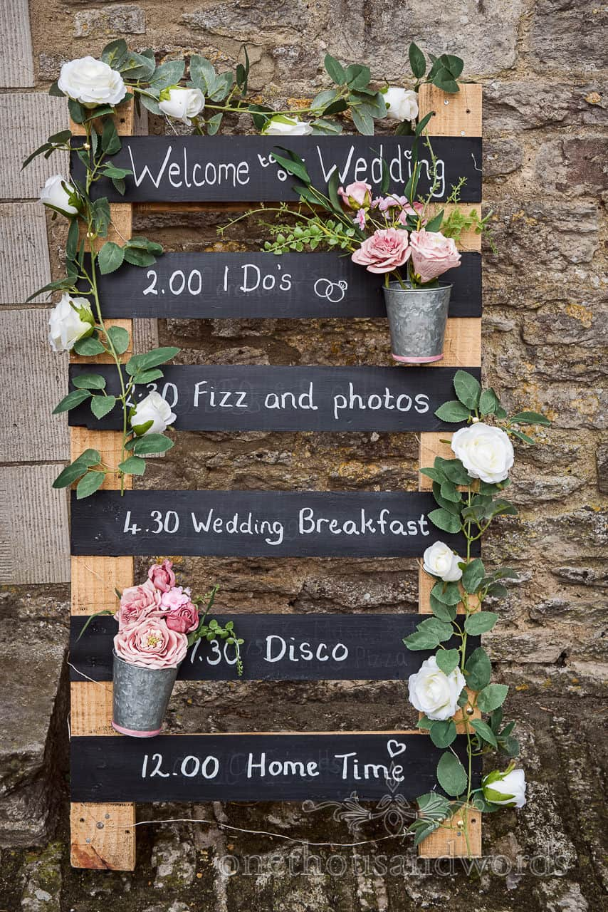 Wooden pallet chalk board custom order of the wedding day sign with foliage and flowers against stone barn wall