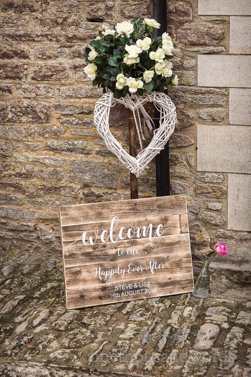 Custom welcome to our happily ever after wooden sign with wicker love heart and flower decorations against stone barn wall
