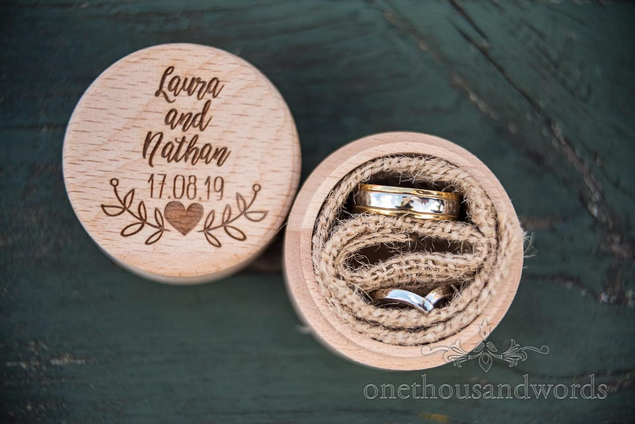 Detail wedding photograph of custom made circular engraved wooden ring box with wedding rings held in hessian