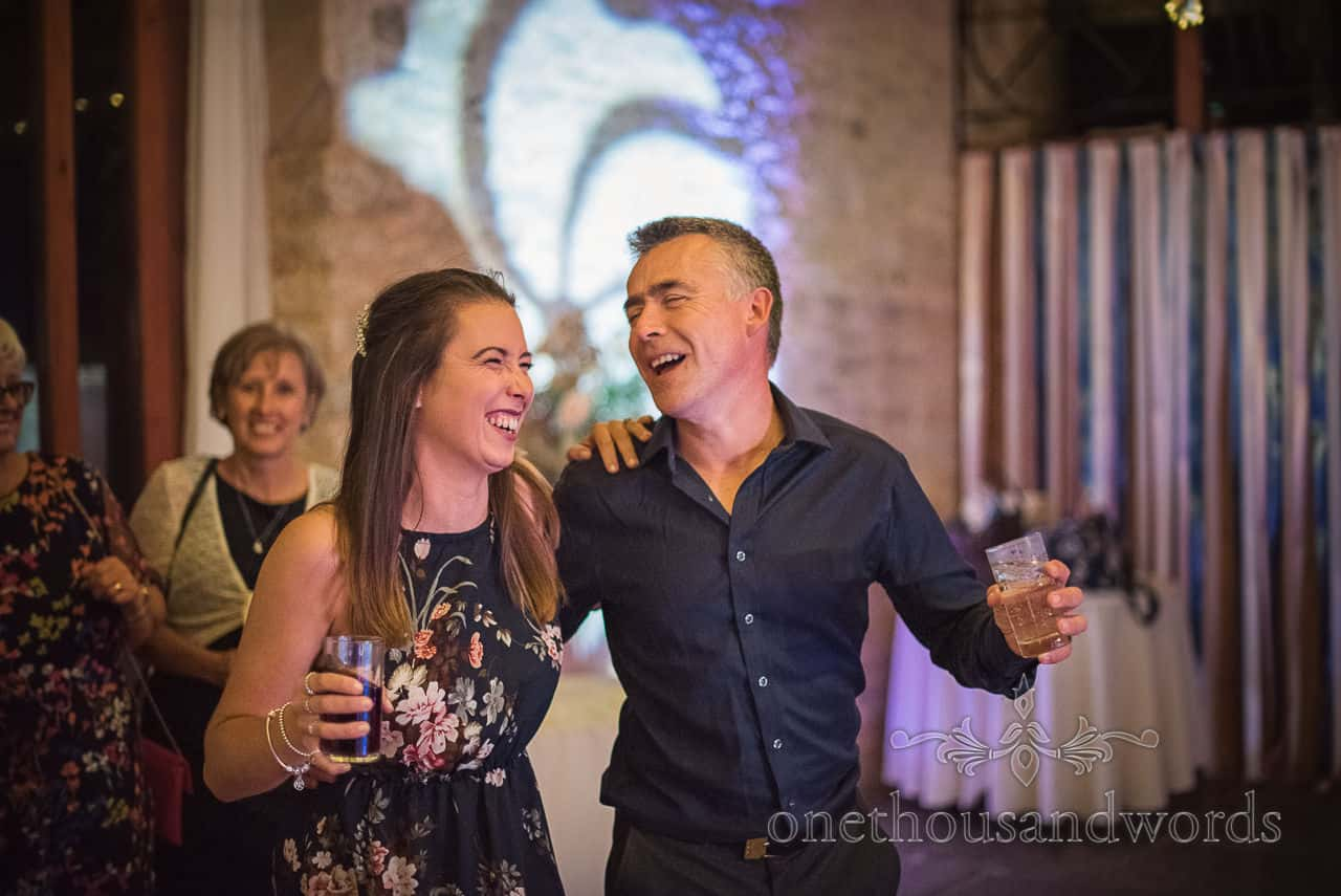 Happy laughing wedding guests dance with drinks in hand during wedding barn reception at Kingston Country Courtyard