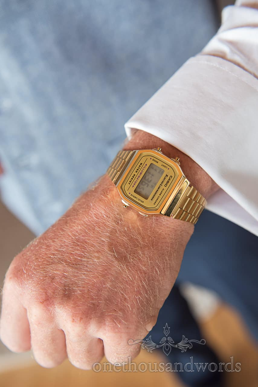 Wedding detail photograph of grooms wrist wearing a vintage retro gold Casio digital watch wedding morning gift