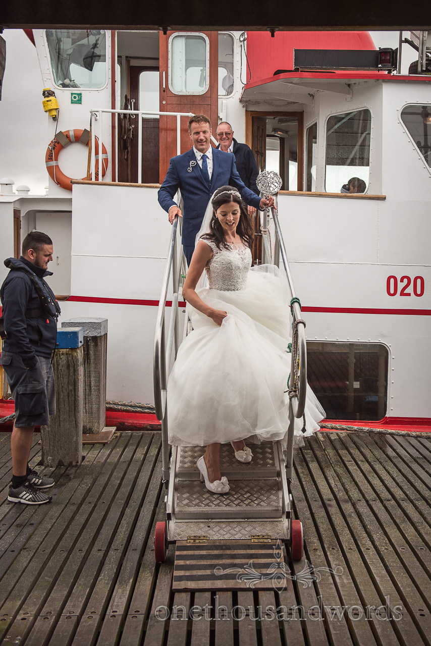 Bride and groom disembark Swanage Ferry onto wooden Victorian pier wedding photo by one thousand words photography