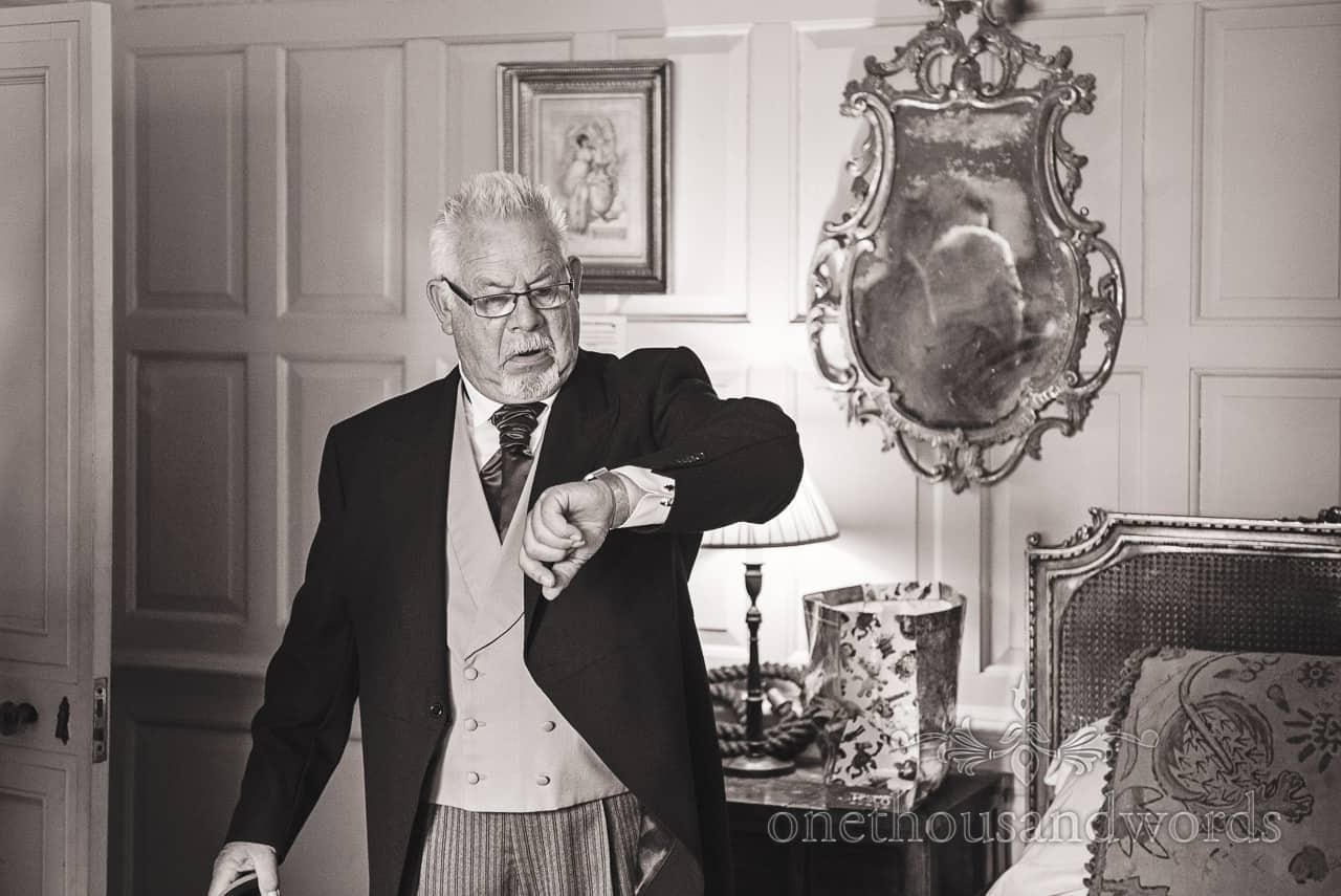 Documentary wedding photograph of bride's father checking his watch for the time during wedding morning preparations