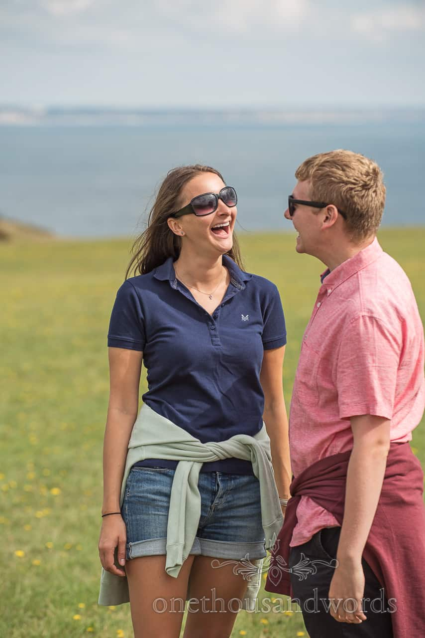 Engagement photo shoot couple relaxing in front of the camera and laughing in the sun at Dorset seaside by one thousand words