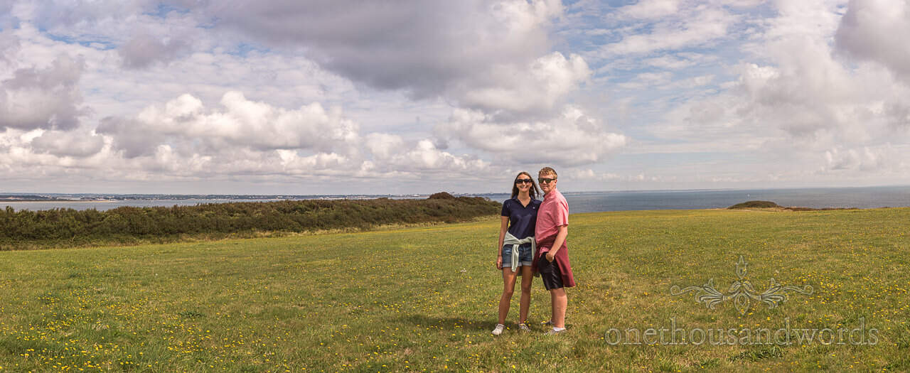 Panoramic photograph from Dorset sea side engagement of happy couple in field with coastal views by one thousand words photography