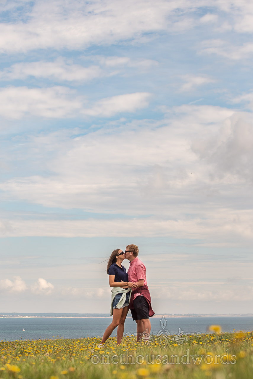 Dorset seaside engagement photograph at Harry's Rocks of couple kissing in field of yellow flowers by one thousand words photography