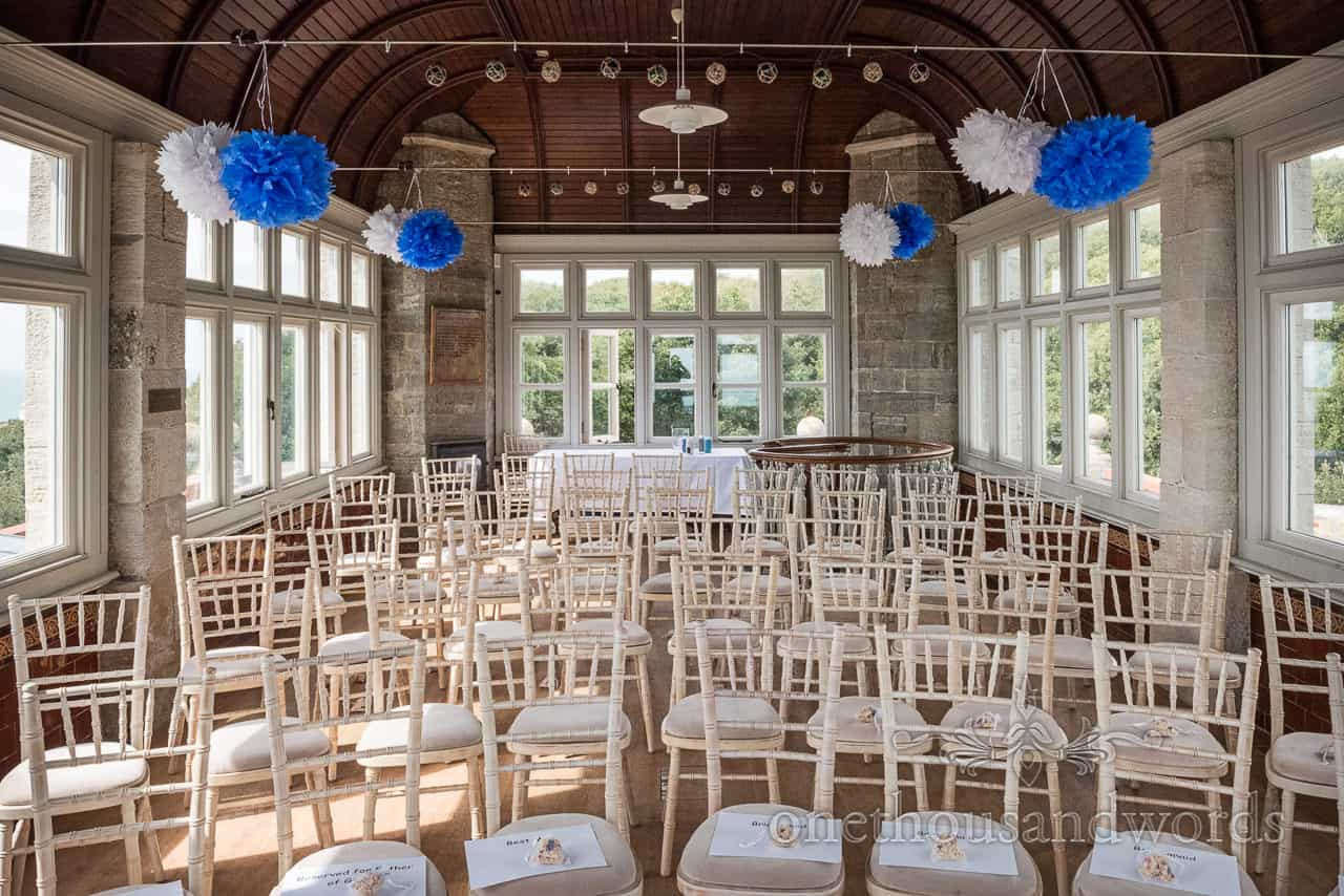 Durlston Castle Belvedere suite civil wedding ceremony room setup with cream chairs and white and blue pom poms