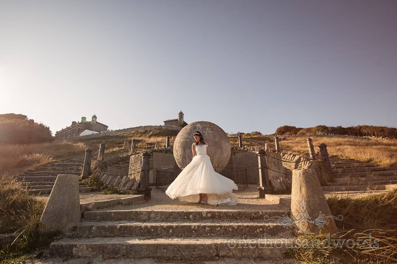 Durlston Castle wedding venue in Dorset photograph of bride spinning in white wedding dress with Victorian stone globe