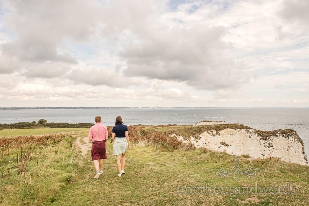 Engaged couple walk towards Old Harry Rocks on Dorset coastal path by one thousand words documentary wedding photography