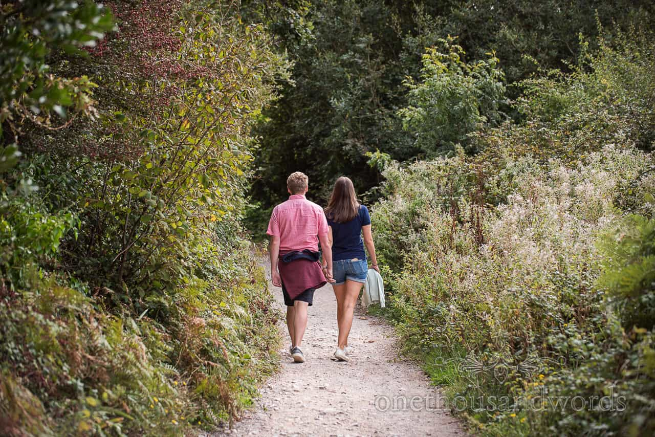 Dorset engagement couple walk hand in hand on country coastal foot path surrounded by green plants photo by one thousand words