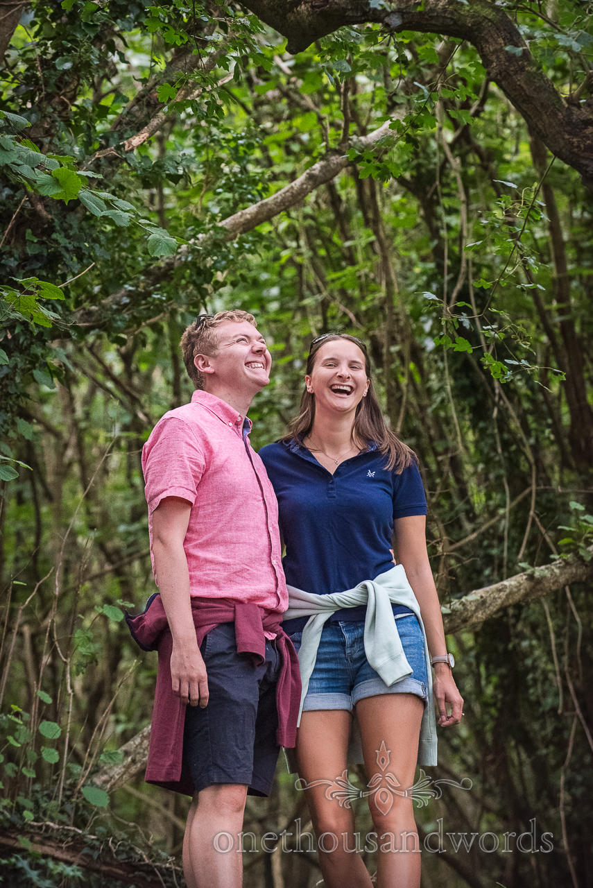 Engagement photograph of couple laughing in Dorset woodland by one thousand words documentary wedding photography