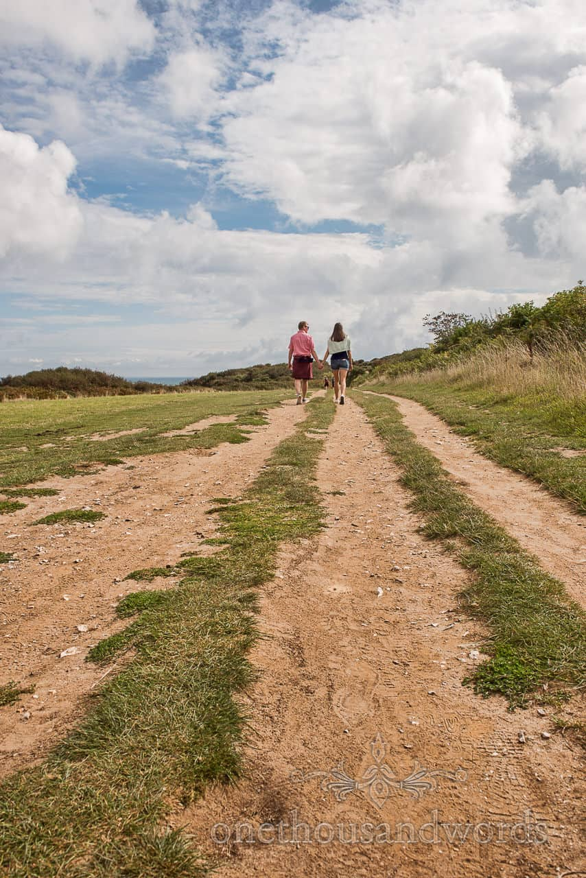 Engagement Photograph Of Couple Walking Toward Old Harry Rocks On Coastal Path by one thousand words wedding photography