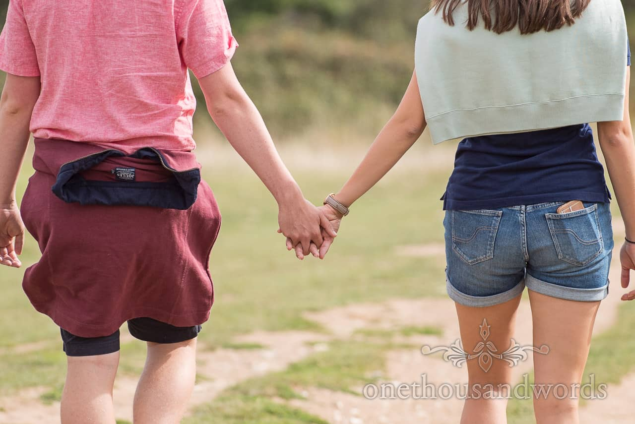 Engagement photograph of engaged couple holding hands in Dorset by one thousand words documentary wedding photography