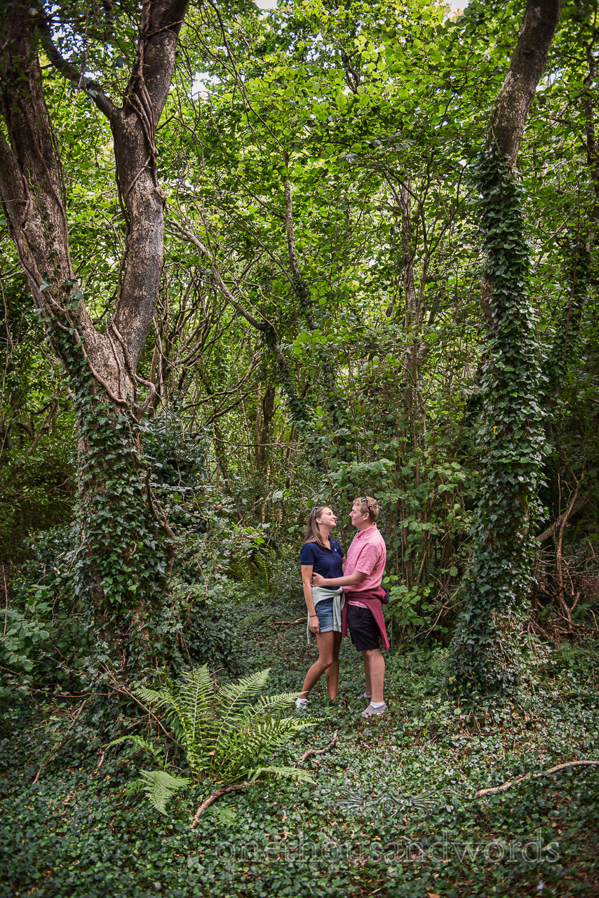 Engagement photograph of couple holding each other in green Dorset woodland by one thousand words wedding photography
