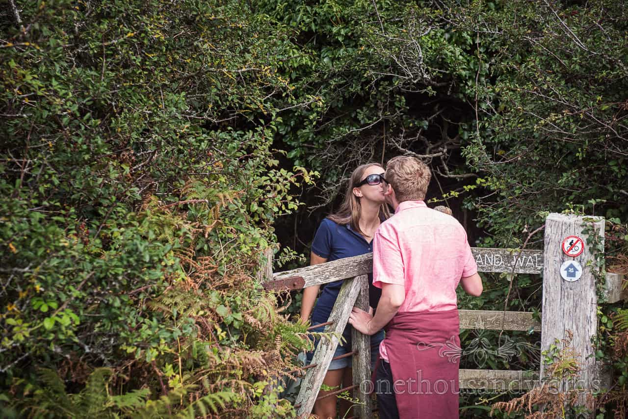 Engaged couple romantically kiss over a kissing gate in Dorset woodland photograph by one thousand words wedding photography