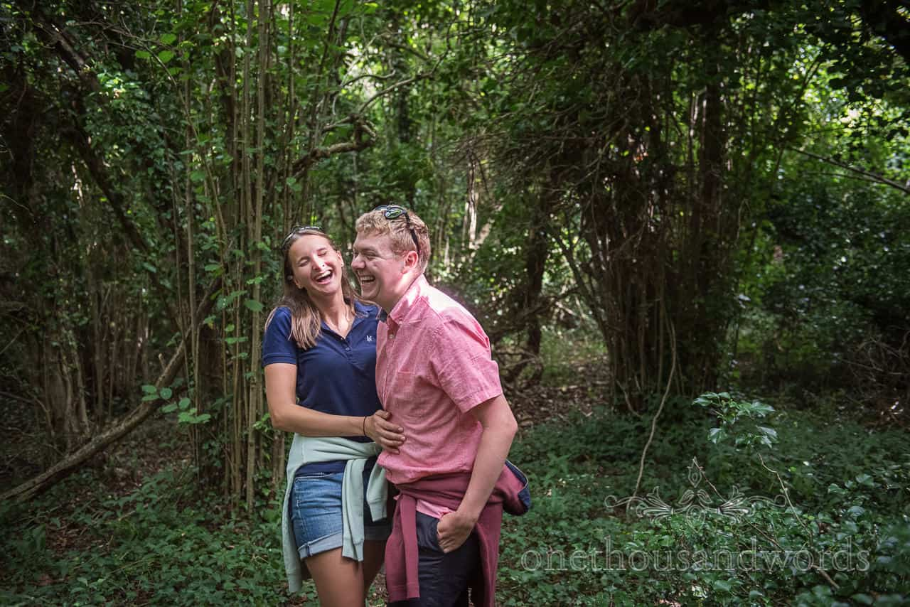 Documentary photograph of engaged couple laughing hard in Dorset woodland by one thousand words wedding photography