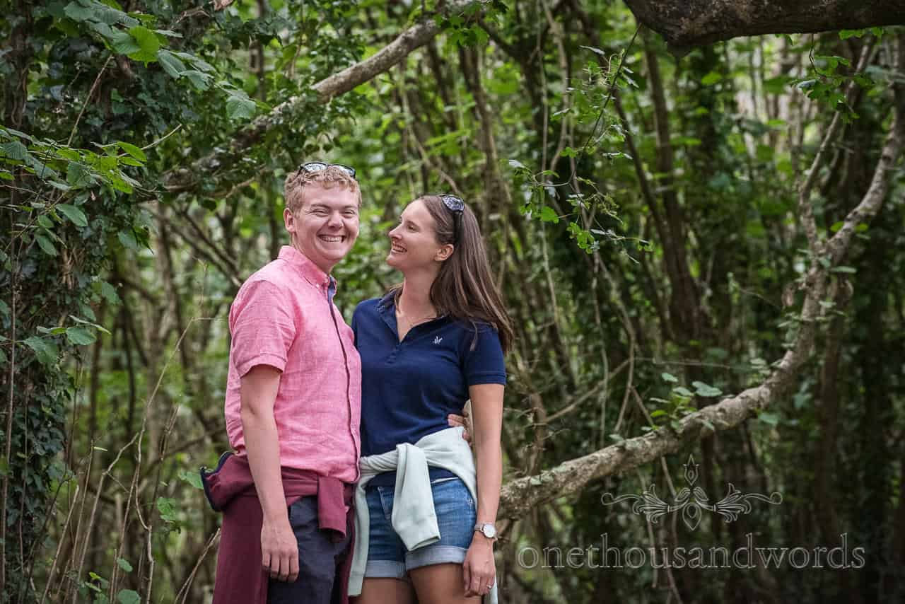 Engagement photo of happy couple hugging in Dorset woodland by one thousand words wedding photographers