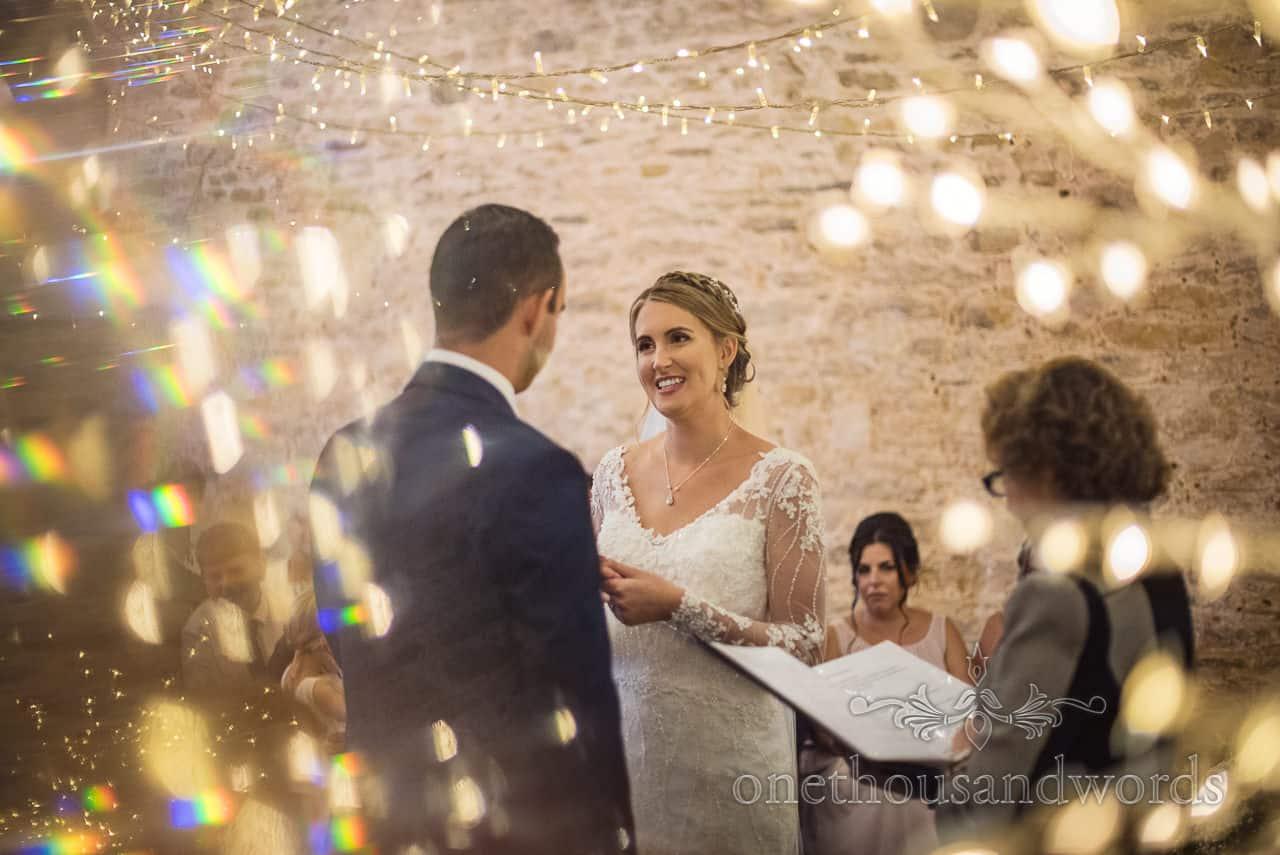 Bride and groom exchange wedding rings under fairy lights at Kingston barn wedding photographs in Dorset