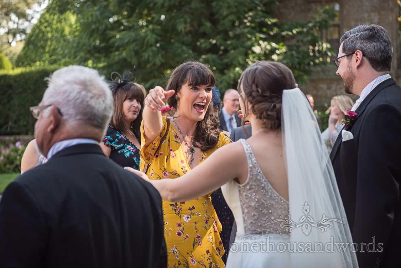 Excited wedding guest wearing yellow floral dress hugs bride in wedding receiving line in gardens