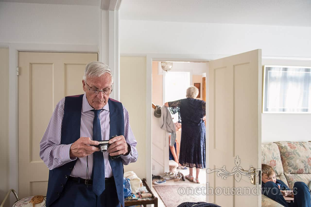 Father of the bride checks his camera during wedding morning preparations by one thousand words documentary wedding photography
