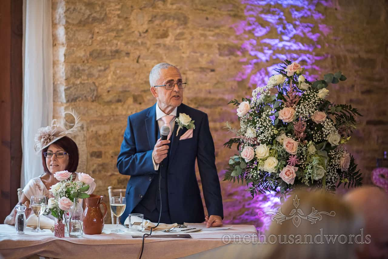 Father of the bride in blue wedding suit delivers wedding speech with microphone at Dorset stone barn wedding